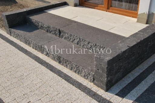 Trawertyn bianco w połączeniu ze stopniami Split nero. Murek oporowy wykonany z  Natulitu Massimo bazaltowy grafit.